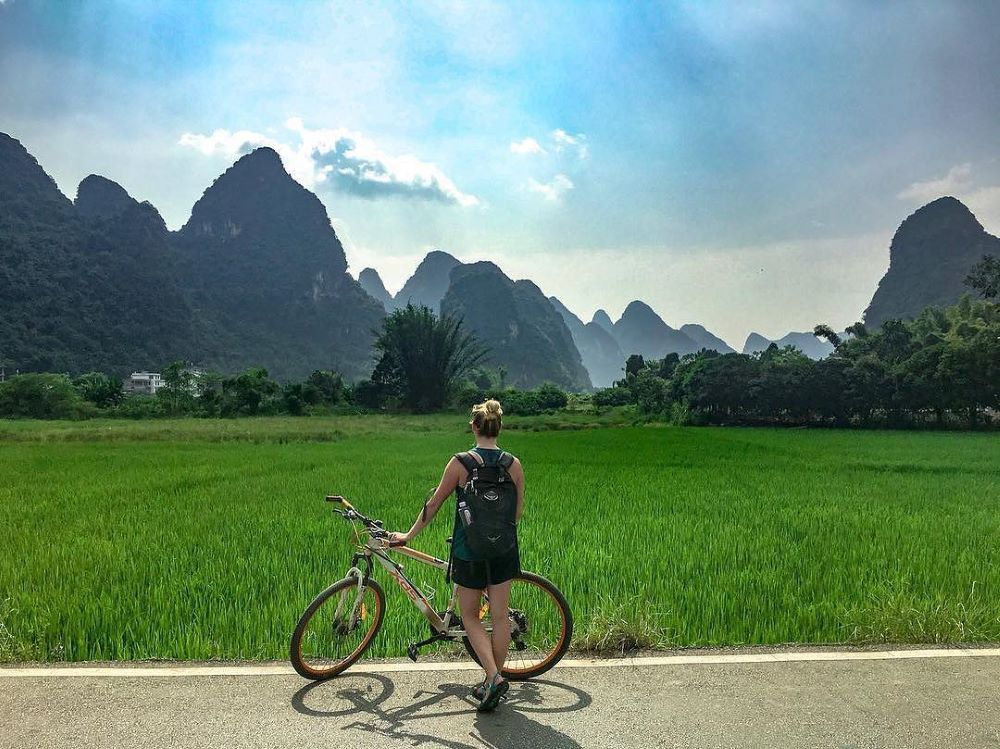 a blond woman serving as her own Yangshuo travel guide stands with a bike in front of a rice field flanked by karst peaks