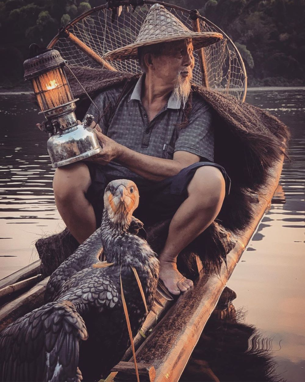 a fisherman with a lantern and a cormorant in a boat on a river outside Yangshuo