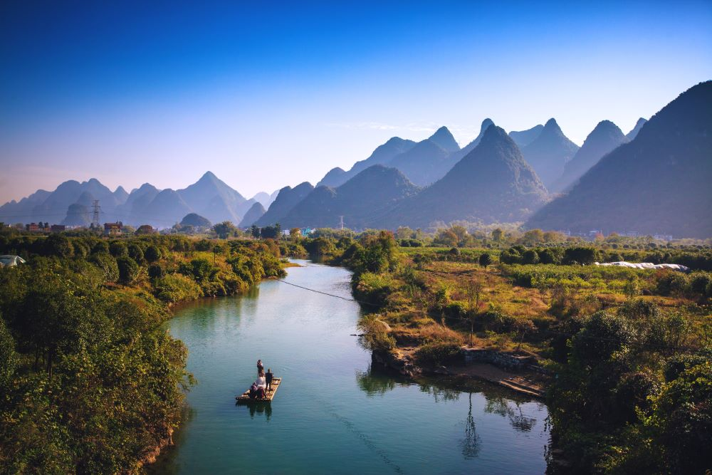 a Yangshuo travel guide and visitors rafting on the Yulong River with karst peaks