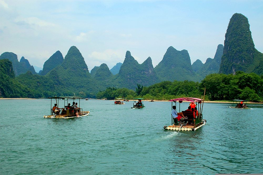 Yangshuo travel guides and visitors ride bamboo rafts on a river