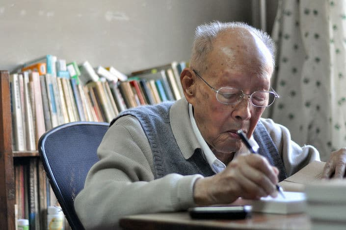 photograph of Zhou Younguang sitting at a desk writing with books in the background
