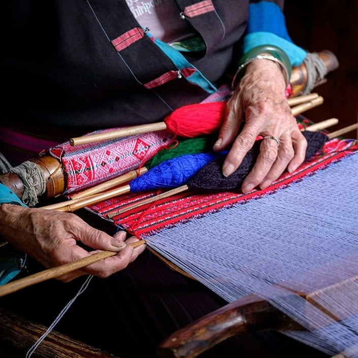 an old woman weaving Chinese Zhuang minority group brocade