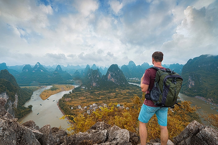a hiker serving as his own Yangshuo travel guide looks out at a forest of karst mountains