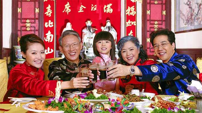 a Chinese family toasting each other over a Chinese holiday meal