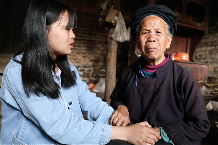 An Chinese old lady is talking to her grand daughter