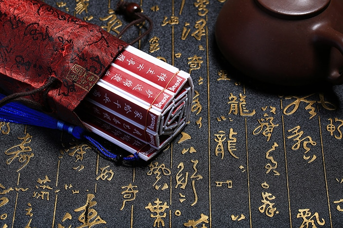 a set of red sticks with white Chinese writing on them in a red silk bag next to a teapot