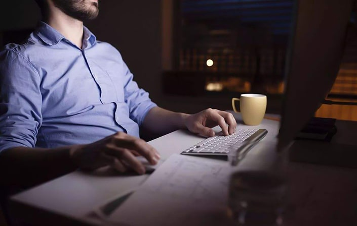 a man sits in front of a computer late at night