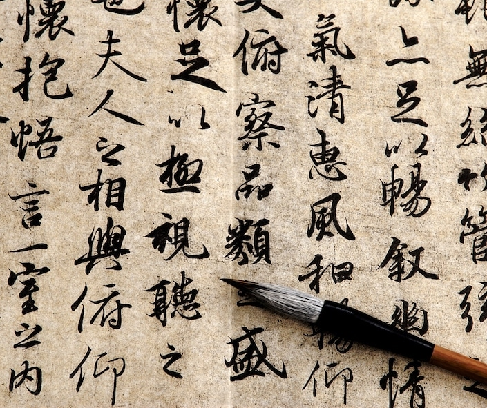 picture of a Chinese calligraphy brush sitting on a paper with Chinese characters written in ink