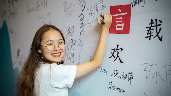 a CLI teacher writing Chinese characters on a wall