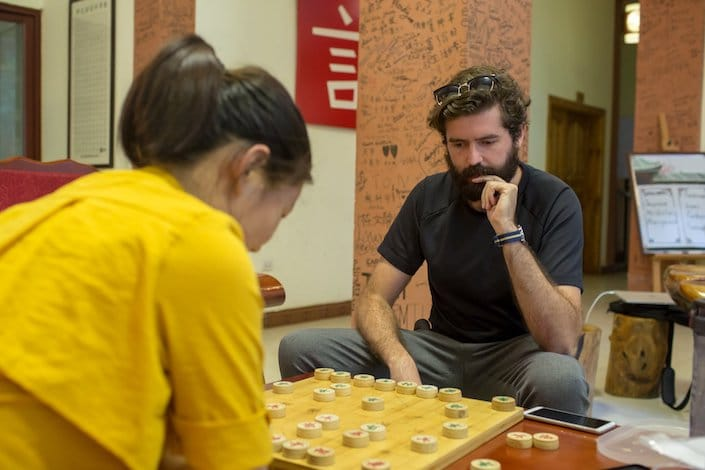 a male and female student playing Chinese chess