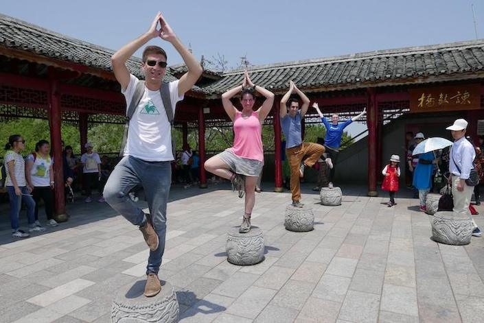 four CLI students posing on top of carved stones in China