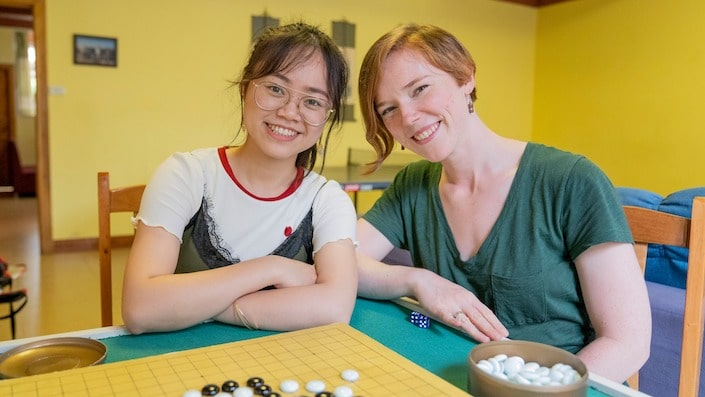 a CLI teacher and student posing with a game of Go