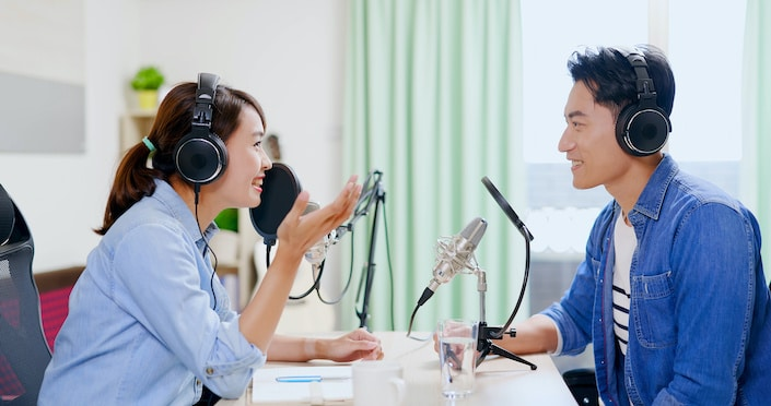 a Chinese man and woman wearing headphones talking to each other while recording a Chinese podcast