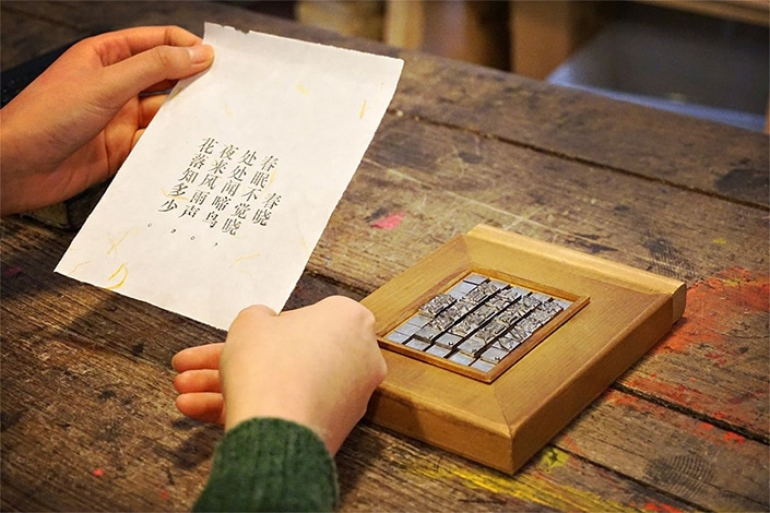pair of hands holding a paper with HSK vocabulary words on it