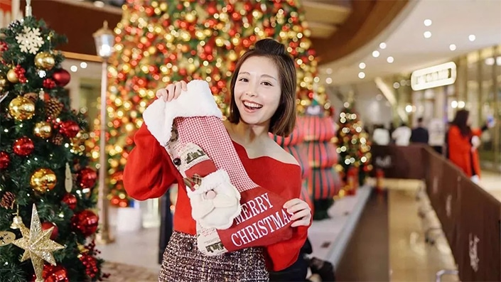 photo of a Chinese woman holding up a Christmas stocking with Christmas trees in the background