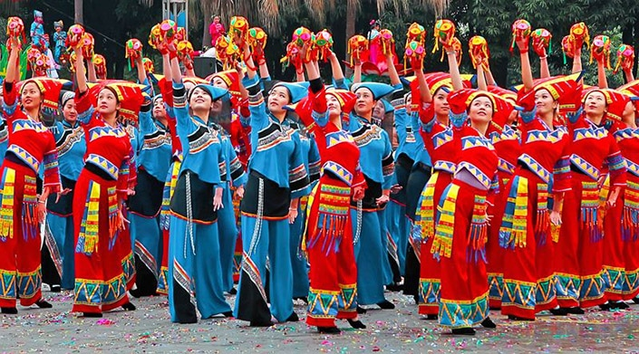 a group of Zhuang women dance with embroidered balls.