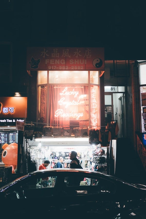a night view of an illuminated store front advertising fortune telling and feng shui
