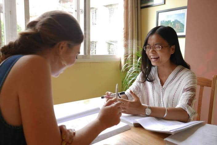 a CLI teacher and student sharing a laugh while studying for the HSK 6
