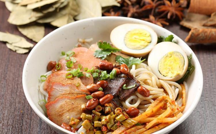 a bowl of Guilin rice noodles with a hard boiled egg, crispy meat and other toppings