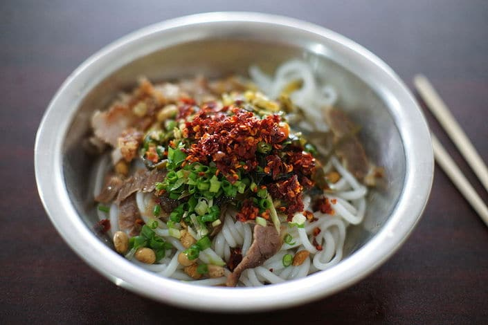 a bowl of Guilin rice noodles topped with ground chili peppers