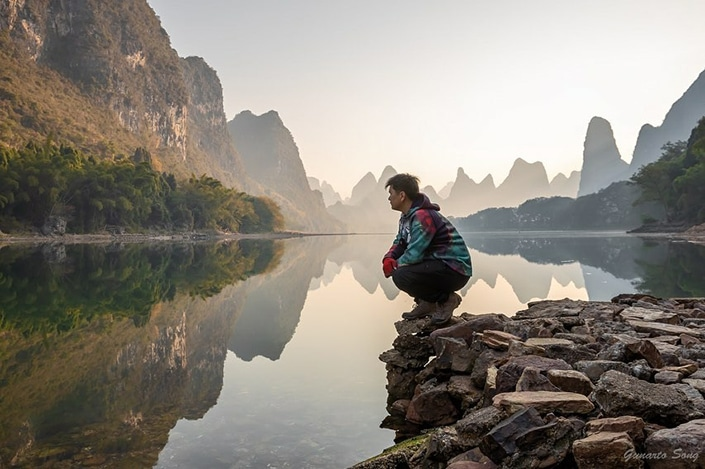 a hiker serving as his own Yangshuo travel guide squats beside a river with karst mountains in the background