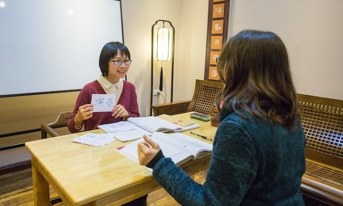 a short haired Chinese woman holding up a flashcard with a Chinese character on it for a female western student seated across from her at a table