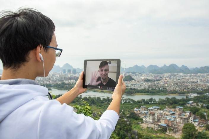 a teacher helping a student learn Chinese on Zoom while standing outside
