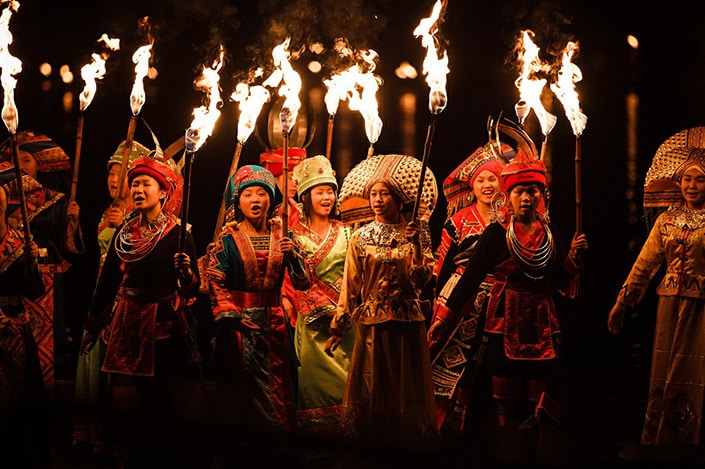 a group of women in Chinese ethnic minority clothes carry torches