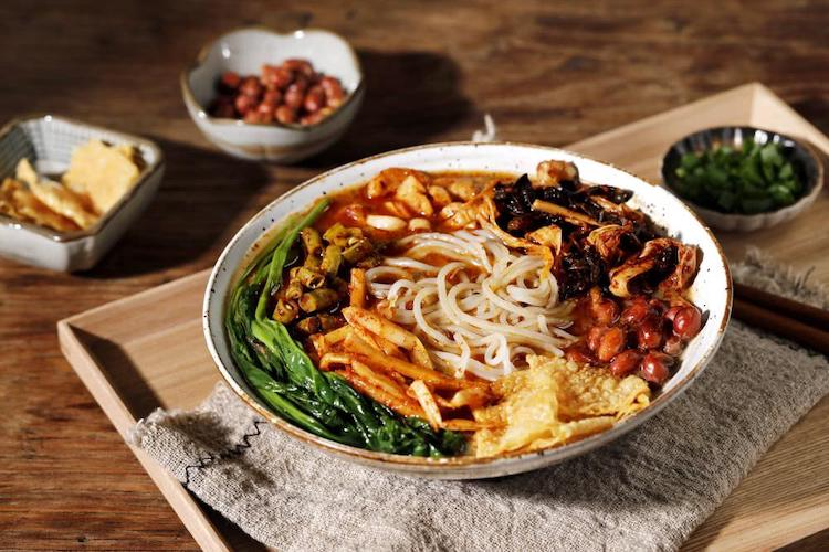 a bowl of Chinese luosifen noodles with lots of toppings.