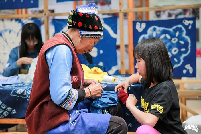 a ethnic minority woman works with cloth as a child looks on