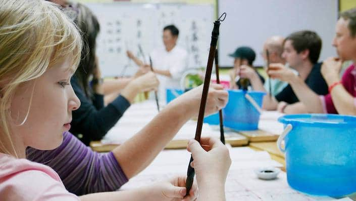 a blond girl holding a Chinese calligraphy brush