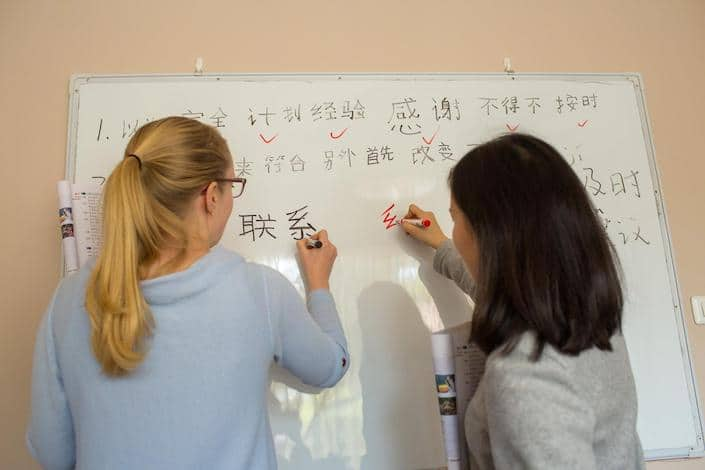 a blond CLI student and her teacher write Chinese characters on a white board