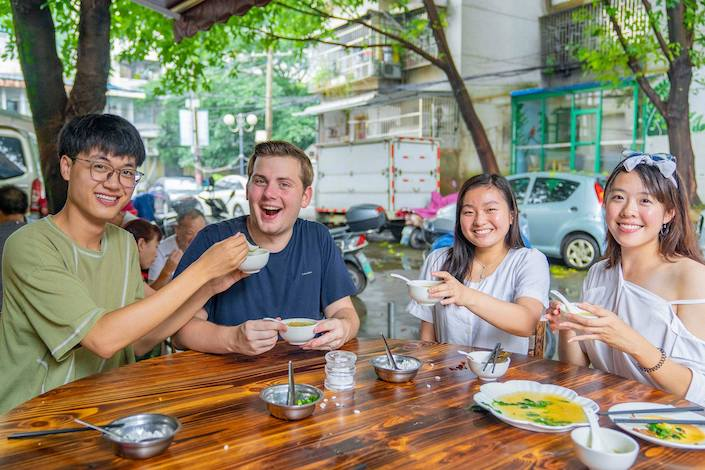 a CLI student eats a meal outdoors beside a road with three Chinese people