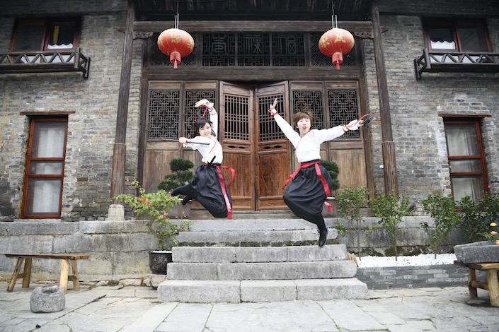 two women holding traditional martial arts weapons jumping into the air in front of a traditional Chinese house with red lanterns