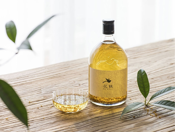 a bottle and cup of osmanthus wine sitting on a wooden table