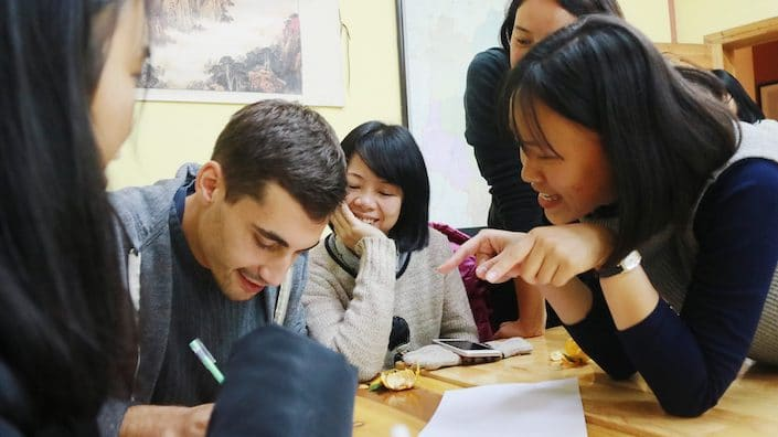 a CLI student practices writing Chinese characters as several CLI teachers look on