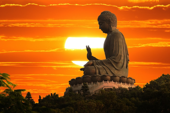 a Buddha statue with one hand raised against a setting sun and orange sky