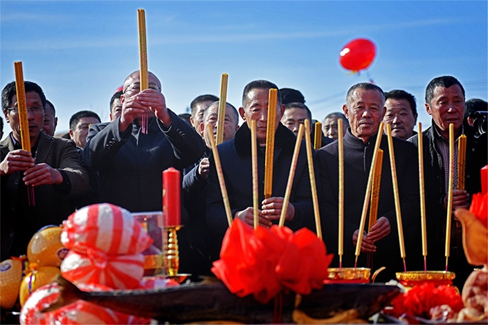 people burning incense during the Chinese holiday called Qingmingjie