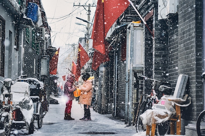 a snowy winter scene showing two people in winter coats standing in an alley with traditional Chinese grey brick buildings and red Chinese flags on either side