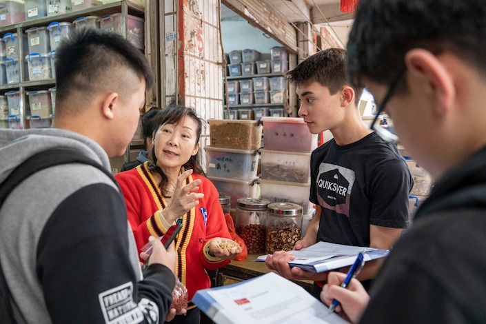 a Chinese woman talks with students about Chinese medicine