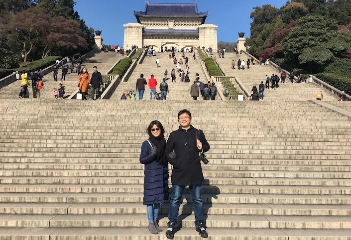 a man and a woman pose on the steps in front  of the Sun Yatsen Mausoleum in Nanjing while other tourists climb the stairs in the background above them