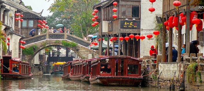 a Suzhou travel guide directs tourists near a canal with traditional houses and red lanterns in the background in Suzhou, China