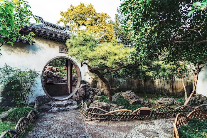 a circular door in a white wall in a traditional Chinese garden, a popular destination for Suzhou travel guides