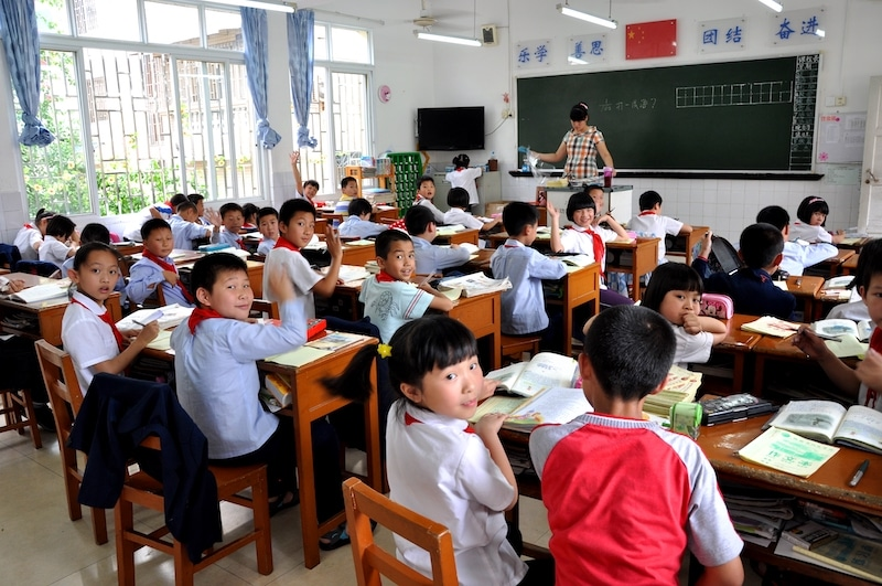 a photo taken from the back of a room showing a classroom full of young Chinese students with a teacher standing in front of a blackboard facing the class