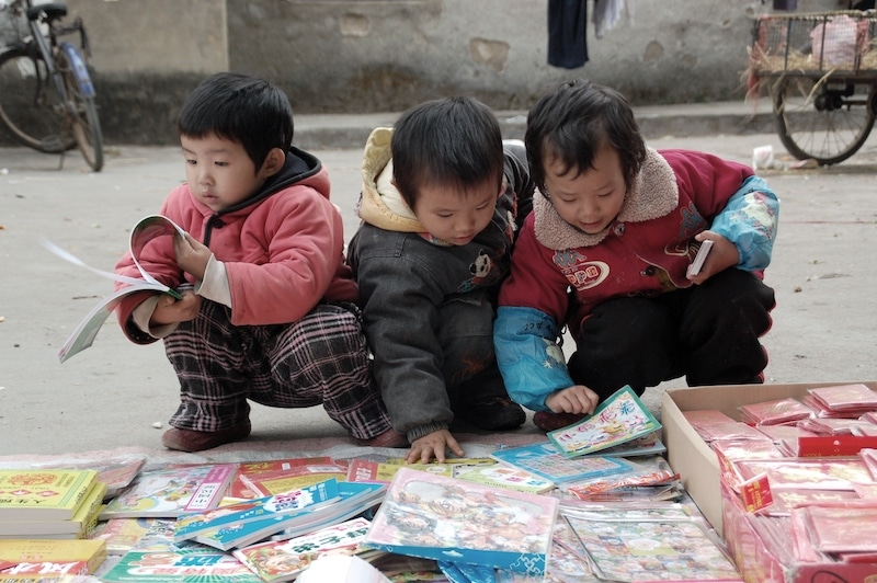 young children in Guilin, China reading books at a second-hand market