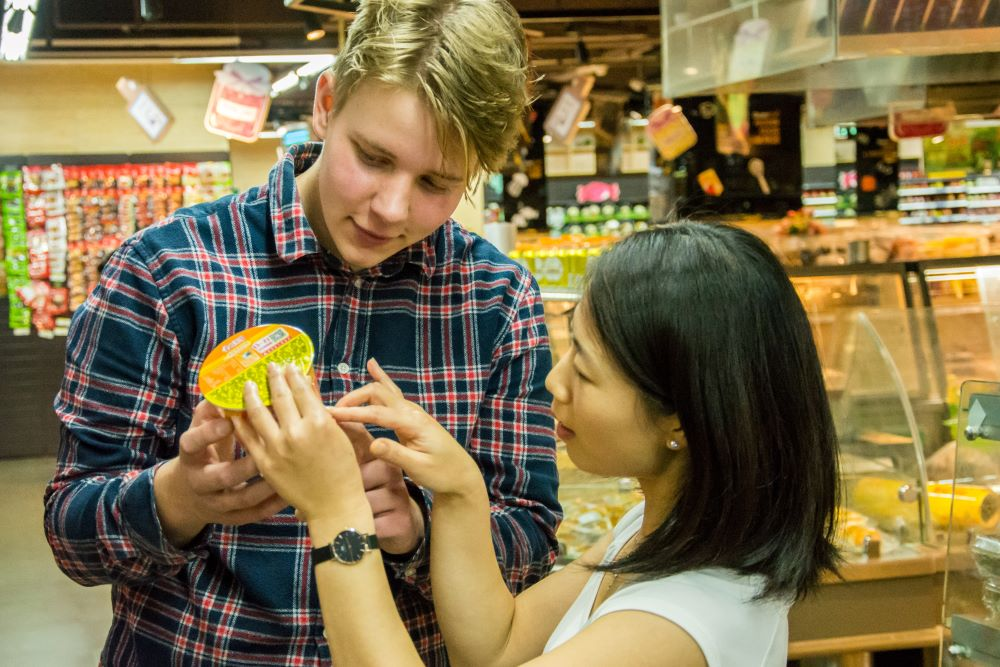 a student and teacher looking at traditional Chinese characters on food at the store