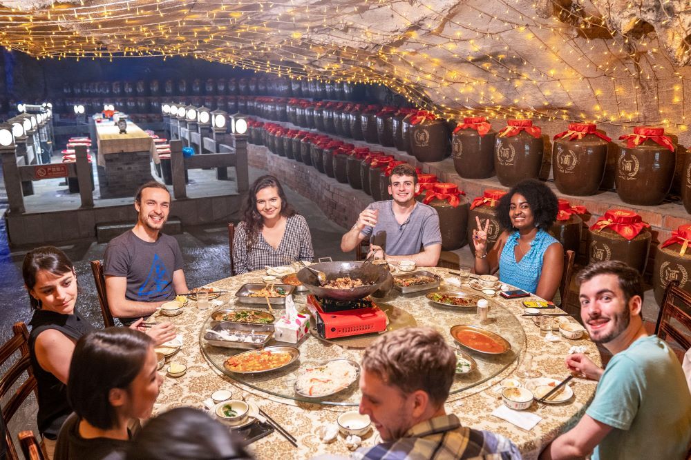 students sit around a table of food in a cave in Guangxi, China