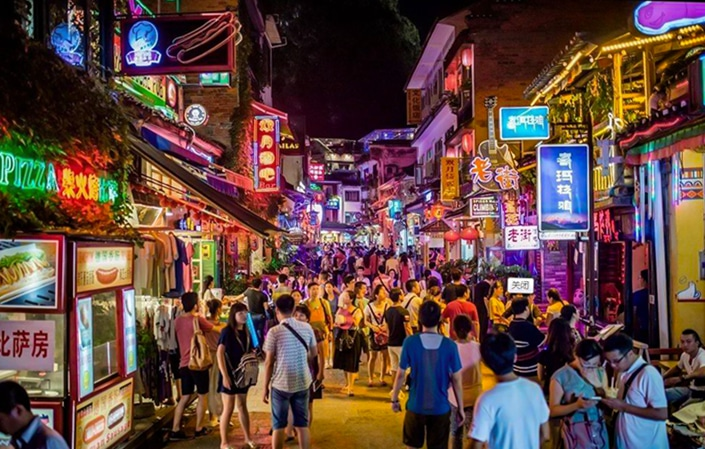 Yangshuo travel guides guide visitors on a walk through the Yangshuo night market