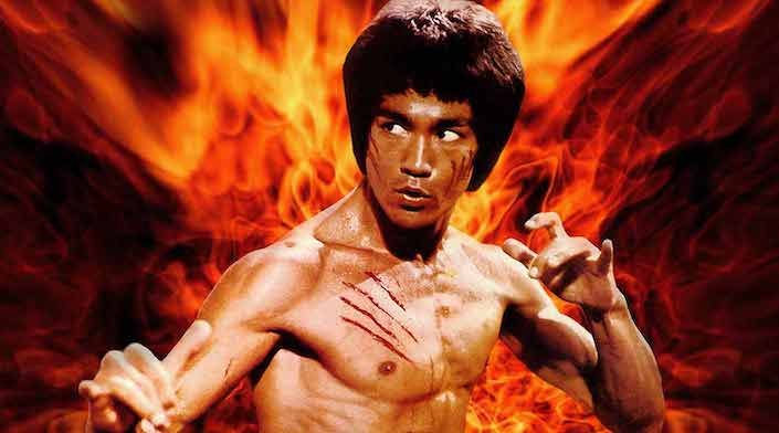 a shirtless Bruce Lee in a Chinese martial arts pose with flames in the background