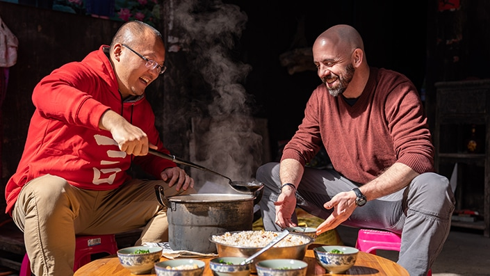 a CLI staff member serving as a Yangshuo travel guide gives a student a ladle of oil tea